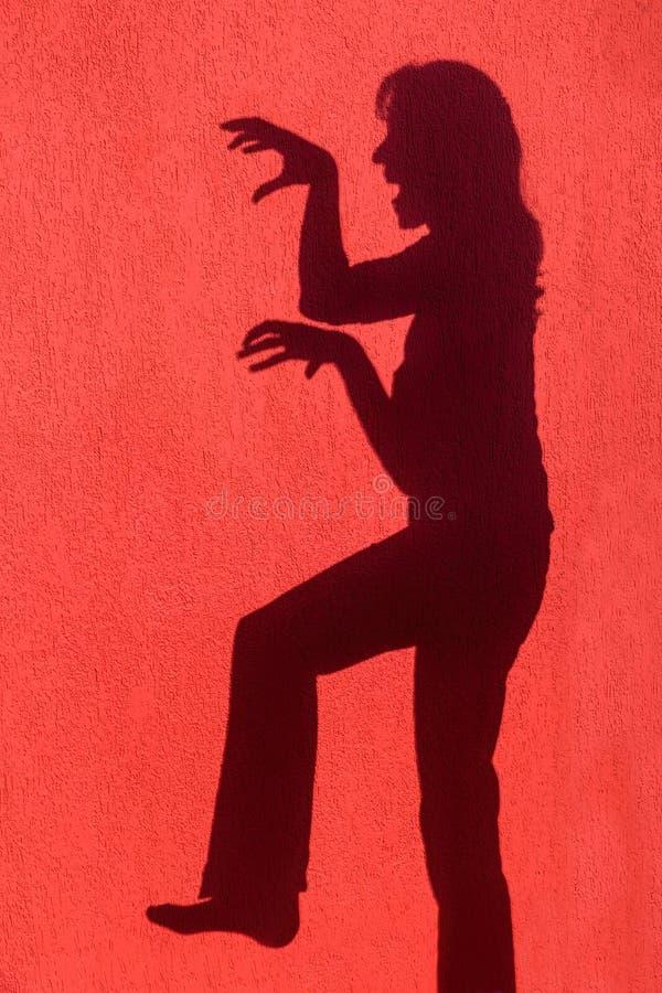 妇女的外形阴影在红色墙壁上的 图库摄影