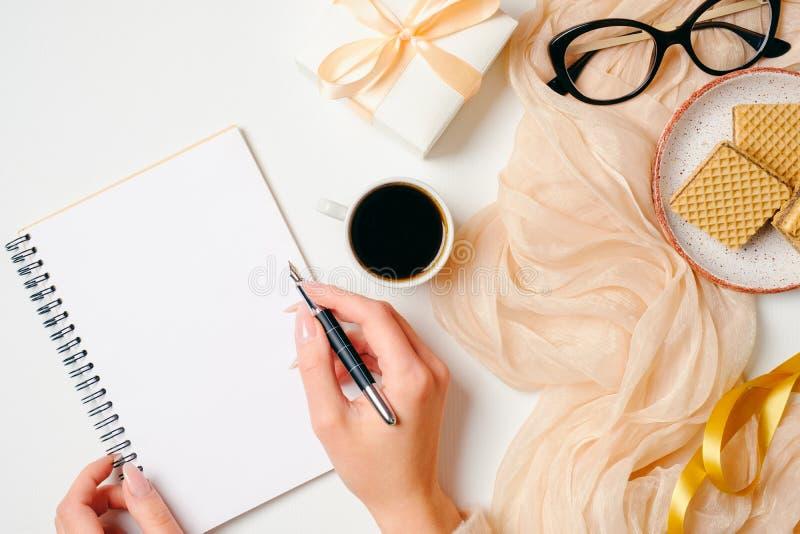 妇女的家庭办公室书桌 工作区用写消息的女性手在纸笔记本和女性金黄时装配件o 库存图片