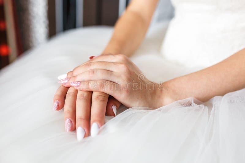 妇女的手在他们的膝盖折叠了预期婚礼和新郎 图库摄影