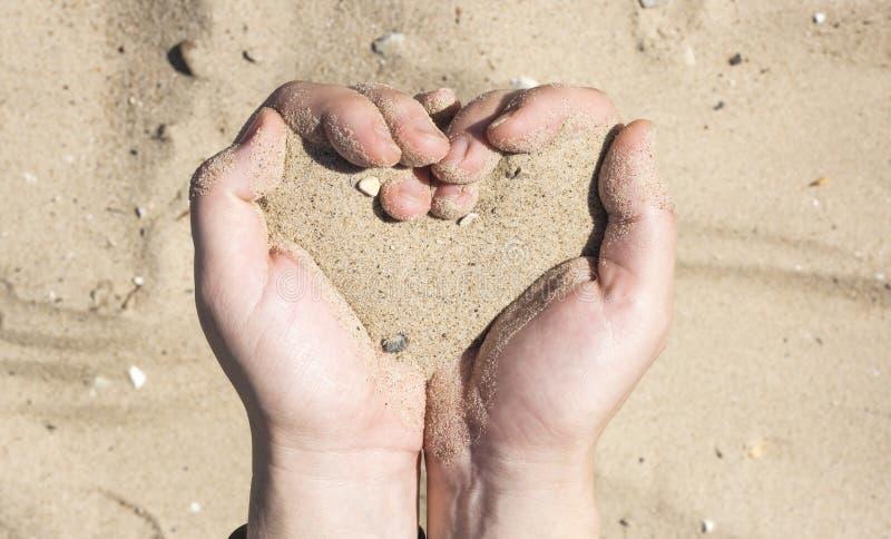 妇女的手在他的手上的拿着沙子以心脏,消失象沙子的生命概念的形式通过手指 图库摄影