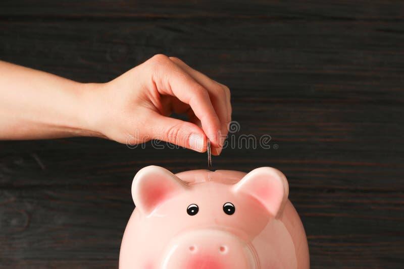 妇女的手在愉快的存钱罐中投入硬币在木桌反对木背景,文本的空间 免版税库存照片