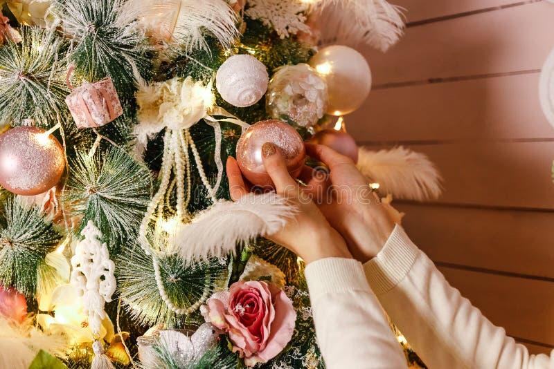 妇女的手垂悬在圣诞树的球 免版税库存照片
