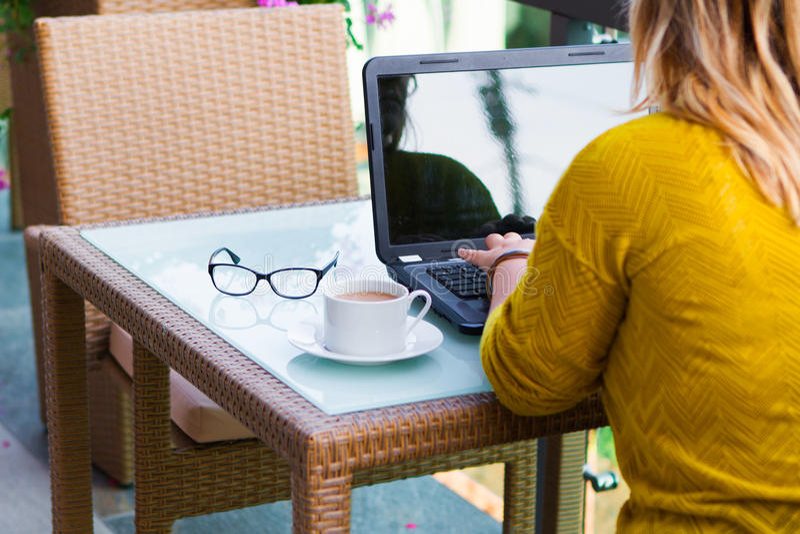 妇女的手她的便携式计算机键盘的  女性研究在街道咖啡馆的膝上型计算机, 图库摄影