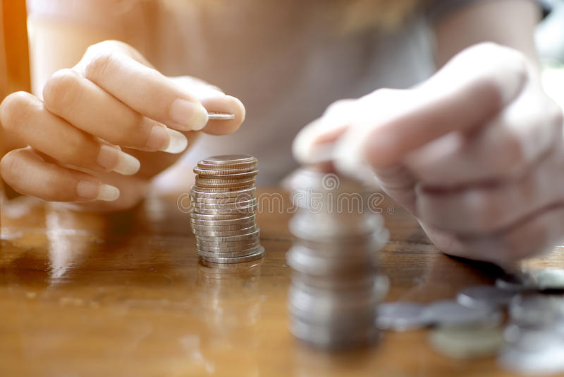 妇女的手把一枚银币放在两堆积的堆顶部在木桌上 免版税库存图片