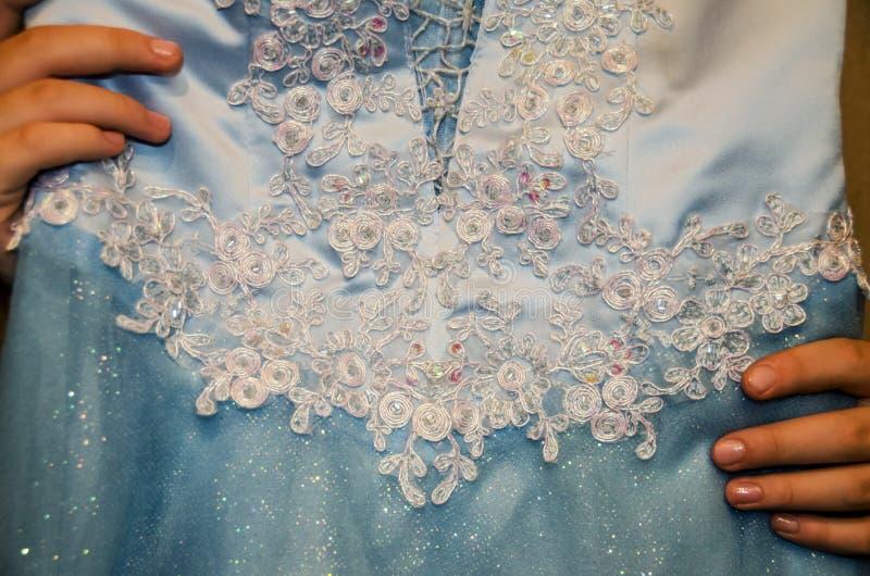 妇女的手拿着一个美丽的蓝色礼服特写镜头 库存照片
