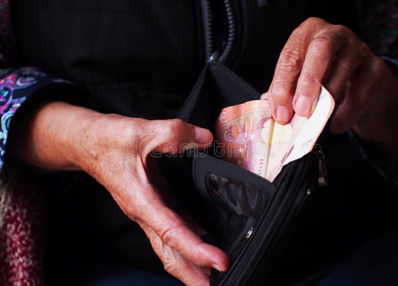 妇女的手拿着一些枚欧元硬币 退休金、贫穷、社会问题和晚年题材  库存照片