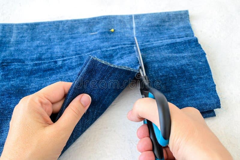 妇女的手拿着剪刀和删去在半蓝色牛仔裤短裤折叠的  缩短与剪刀和缝合的牛仔布短裤 图库摄影