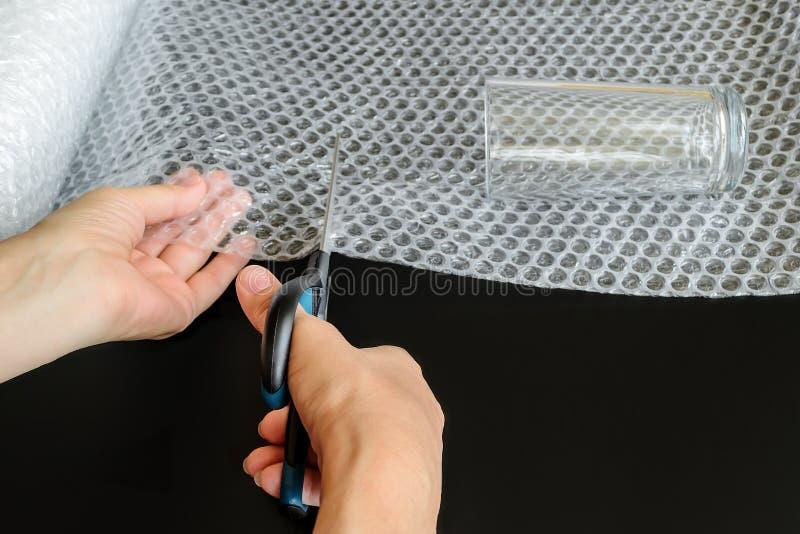 妇女的手拿着剪刀和削减白色透明磁泡线厘片断为包裹玻璃 o 免版税库存图片
