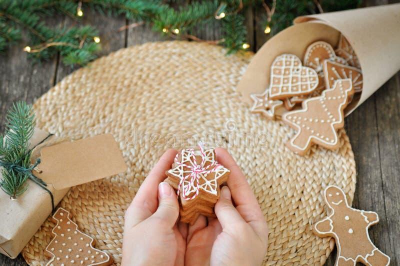 妇女的手拿着自创圣诞节姜饼曲奇饼用结霜在美好的木背景的糖 圣诞树de 免版税图库摄影