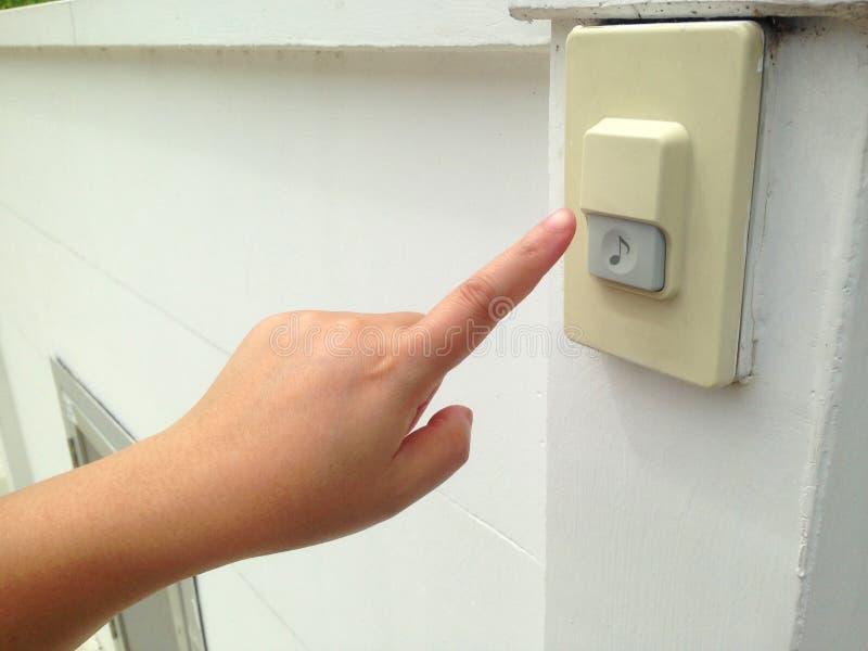 妇女的手按在房子前面的门铃 图库摄影
