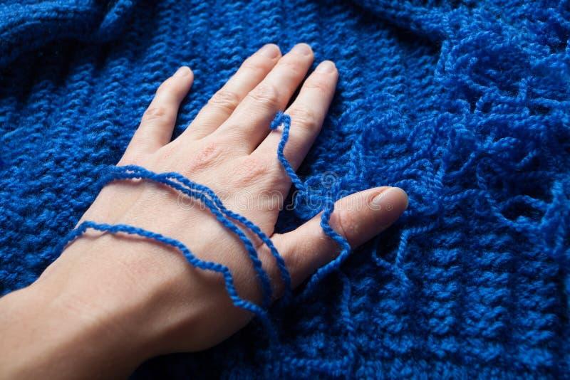 妇女的手接触蓝色柔和的光和宜人的毛线,编织的螺纹,自创衣裳 免版税库存照片
