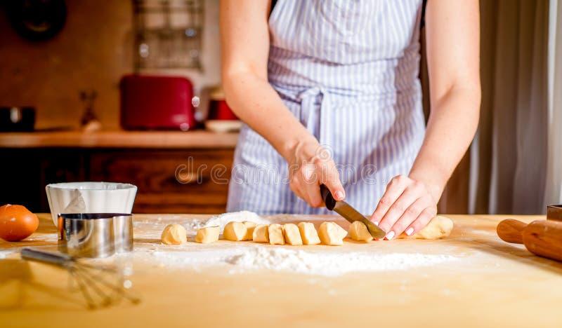 妇女的手揉在桌上的面团 库存图片