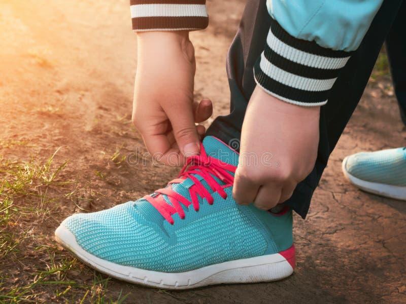 妇女的手根据早晨系带在土路的蓝色运动鞋或平衡太阳 免版税库存照片