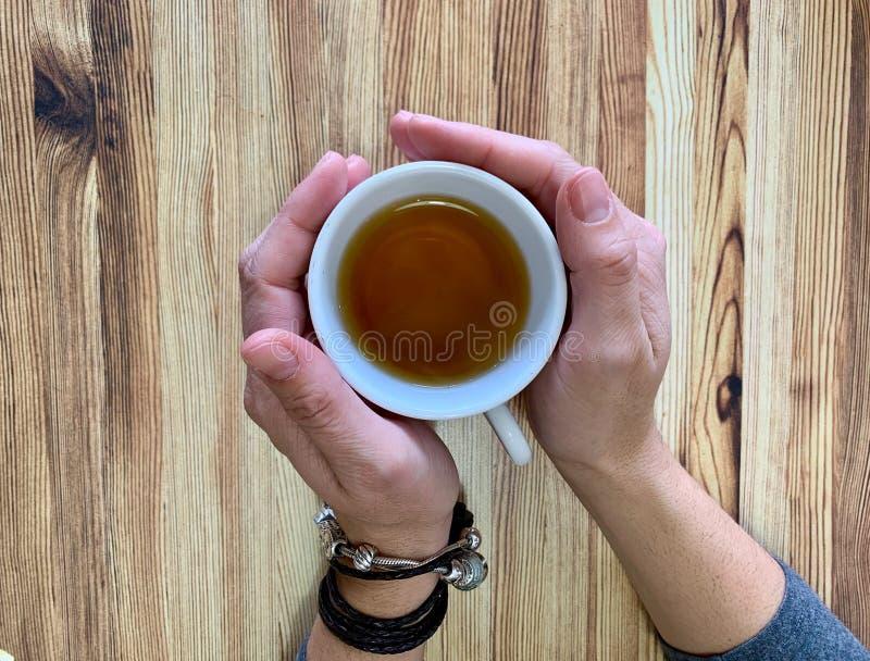 妇女的手特写镜头有拿着一杯茶的镯子的 库存照片