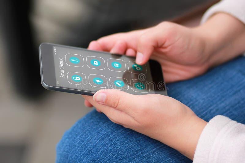 妇女的手特写镜头有黑智能手机和聪明的家庭应用象接口设计的 议院自动化 免版税库存照片
