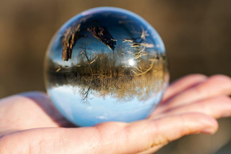 妇女的手藏品清楚石英Sphere反射的湖,森林,天空 库存照片