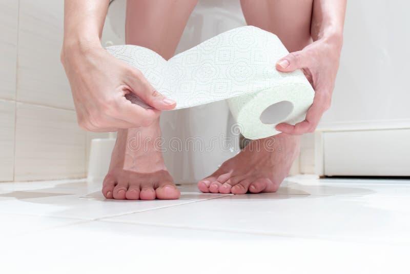 妇女的播种的腿,坐与被降下的内裤和手纸卷的一间洗手间在她的手上 概念图象  免版税图库摄影