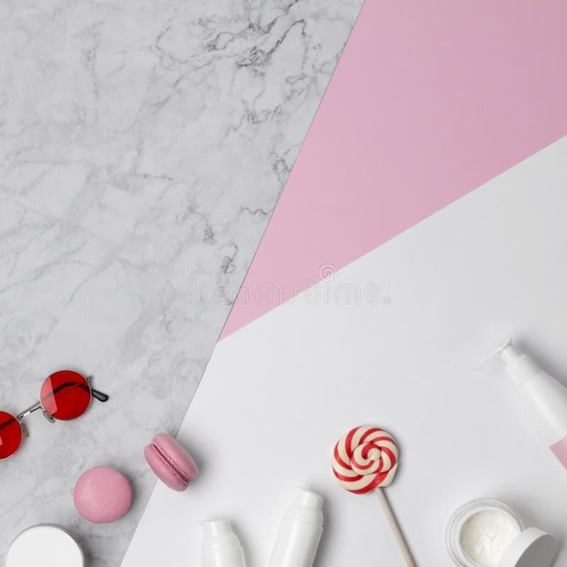妇女的有辅助部件、装饰化妆用品和甜点的秀丽书桌顶视图在桃红色,大理石和白色淡色桌上 免版税库存图片