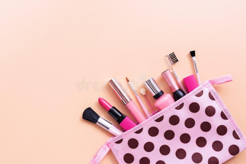 妇女的构成的各种各样的化妆用品在粉红彩笔背景的一个化妆袋子 o 库存图片