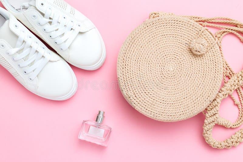 妇女的柳条提包和白色运动鞋有香水的在桃红色背景 r 库存图片