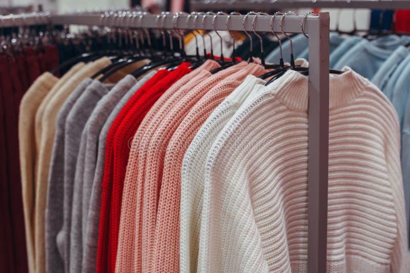 妇女的桃红色做看起来在挂衣架的苗条吊 衣裳销售在商店 库存照片
