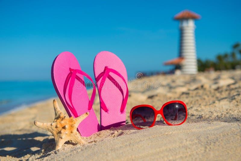妇女的海洋辅助部件:凉鞋、太阳镜和海星在热带沙子靠岸以灯塔为背景 免版税库存图片