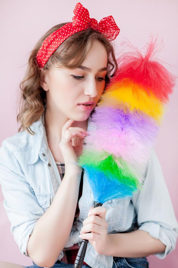 妇女的清洗的别针 微笑的画报女孩拿着五颜六色的喷粉器刷子 清洁服务 画报与羽毛喷粉器的女孩擦净剂 免版税库存图片