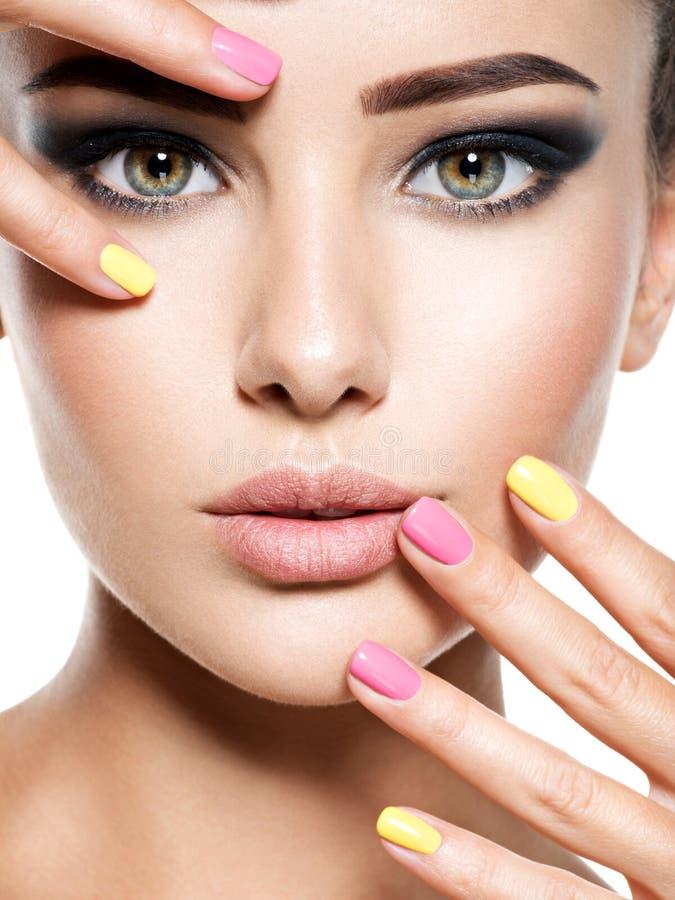 妇女的特写镜头面孔有多彩多姿的钉子的 免版税库存图片