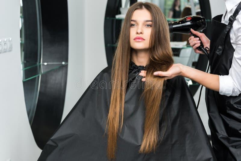 妇女的美发师干毛发 免版税库存照片