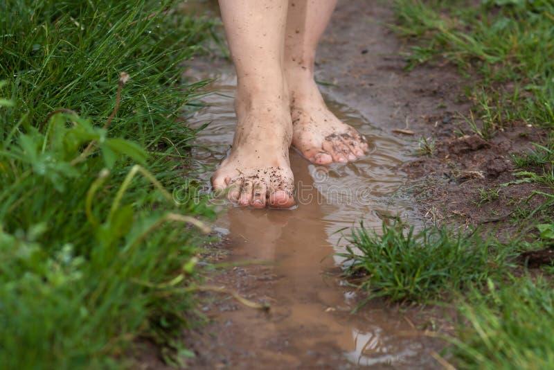 妇女的脚水坑的在雨,特写镜头以后 免版税库存照片
