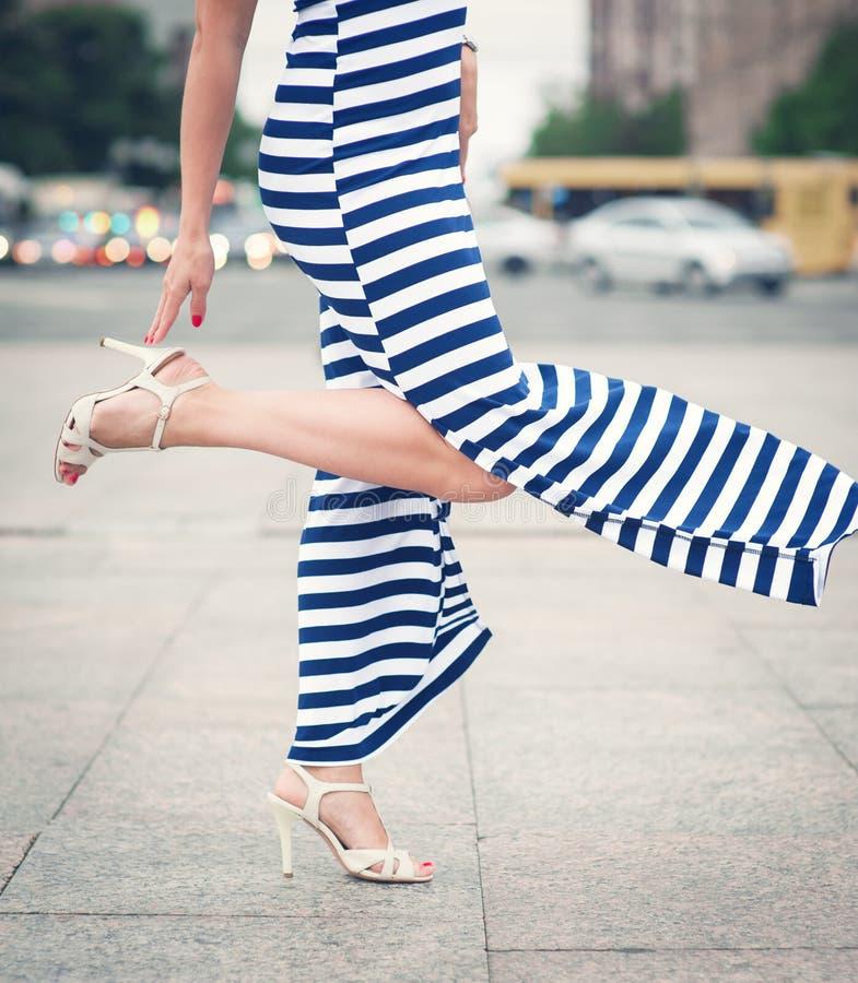 妇女的腿有高跟鞋的穿戴了长期镶边的礼服 图库摄影