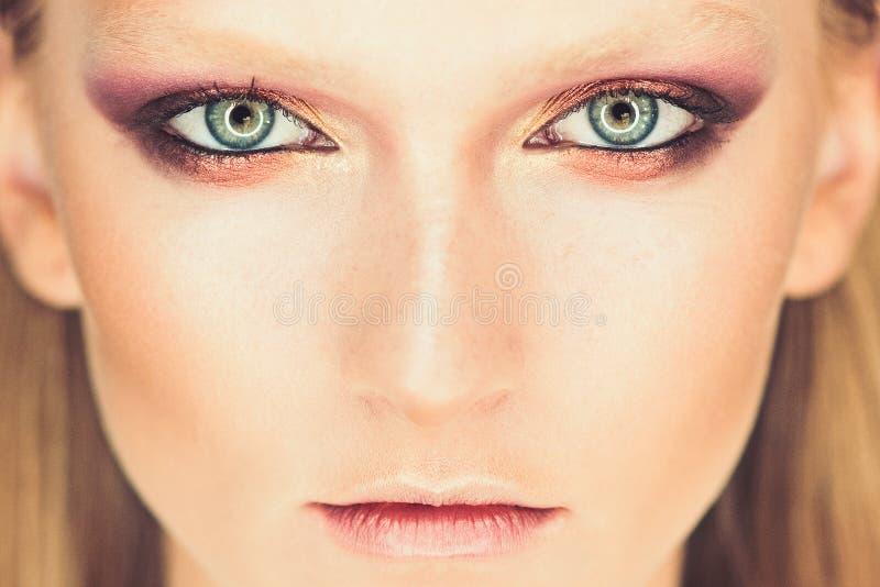 妇女的蓝眼睛有美丽的金黄树荫和黑眼线膏构成的 经典之作组成 完善的眉头引导和嘴唇 免版税库存图片