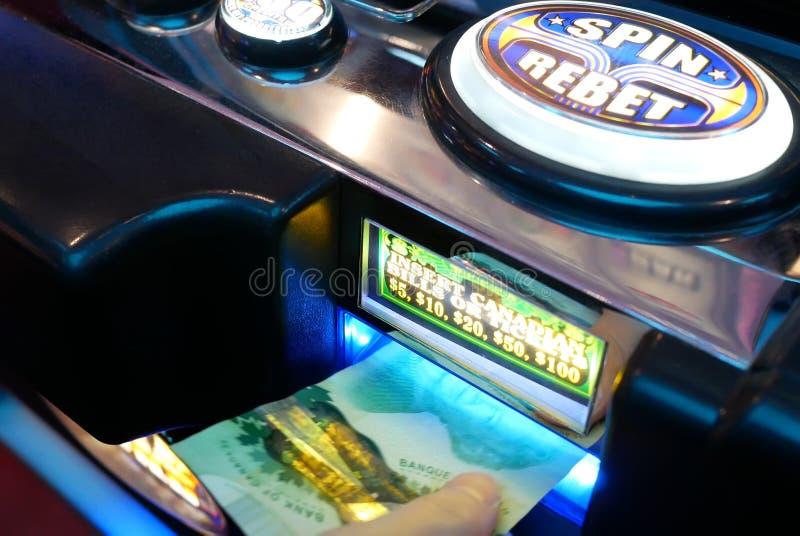 妇女的行动插入在老虎机的金钱在Casin里面 库存照片