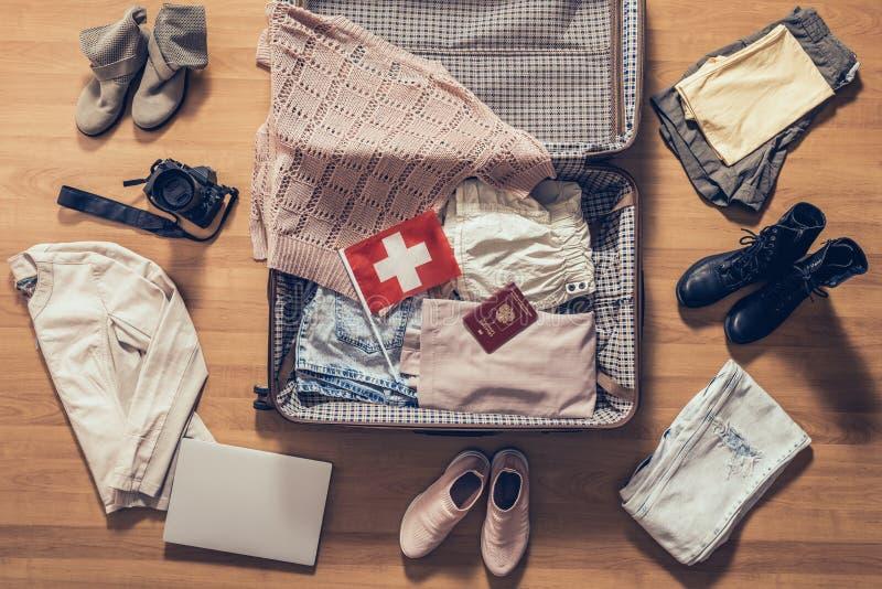 妇女的衣裳、膝上型计算机、照相机、俄国在镶花地板上的瑞士的护照和旗子在和在开放suitcas附近 库存图片