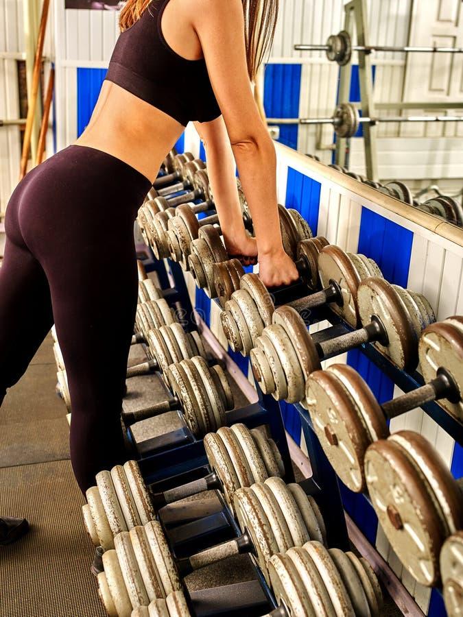 妇女的身体局部与哑铃一起使用在健身房 免版税图库摄影