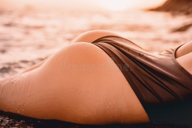 妇女的身体放松海上有日落颜色的黑游泳衣的 免版税库存图片