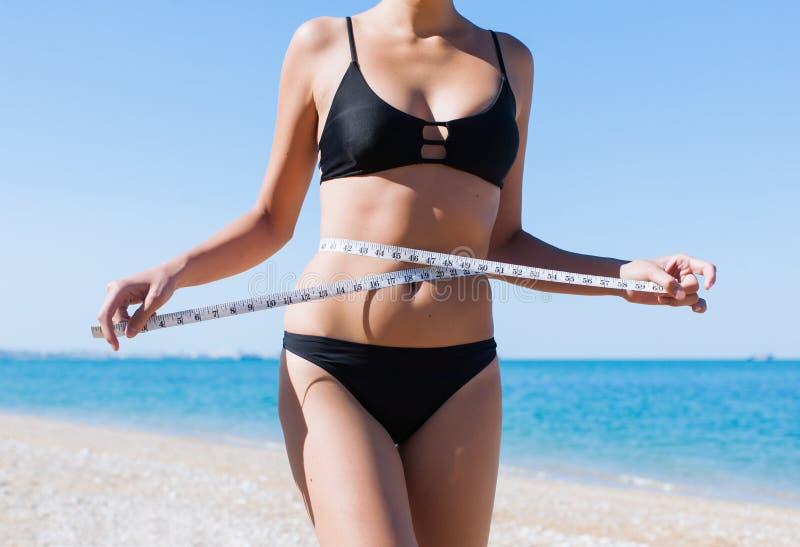 妇女的躯干比基尼泳装的有在海滩的卷尺的 图库摄影