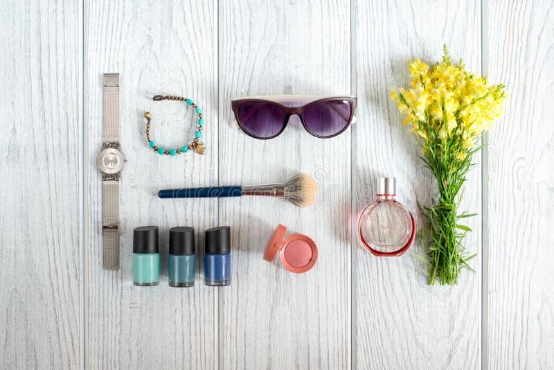 妇女的辅助部件、化妆用品和野花 库存图片
