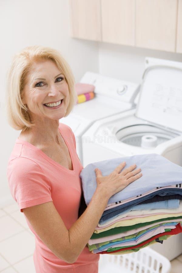 妇女的运载的被折叠的洗衣店 库存图片