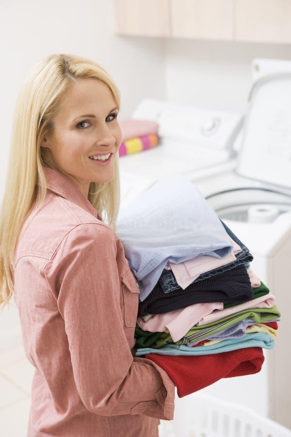 妇女的运载的被折叠的洗衣店 库存照片
