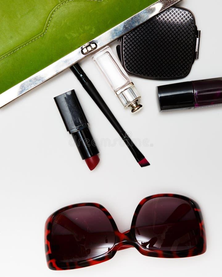 妇女的顶视图辅助部件 时髦的太阳镜,绿色袋子,唇膏,香水,塑造在白色的平的位置 库存图片