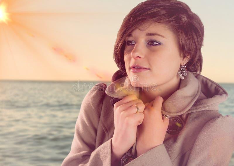 妇女的综合图象外套的反对有火光的海 库存例证