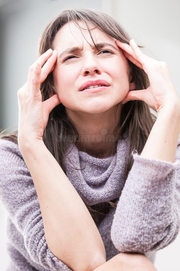 妇女的头疼的被强调的表示 库存照片