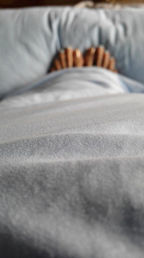 妇女的blury脚在浅兰的色的床上 免版税图库摄影