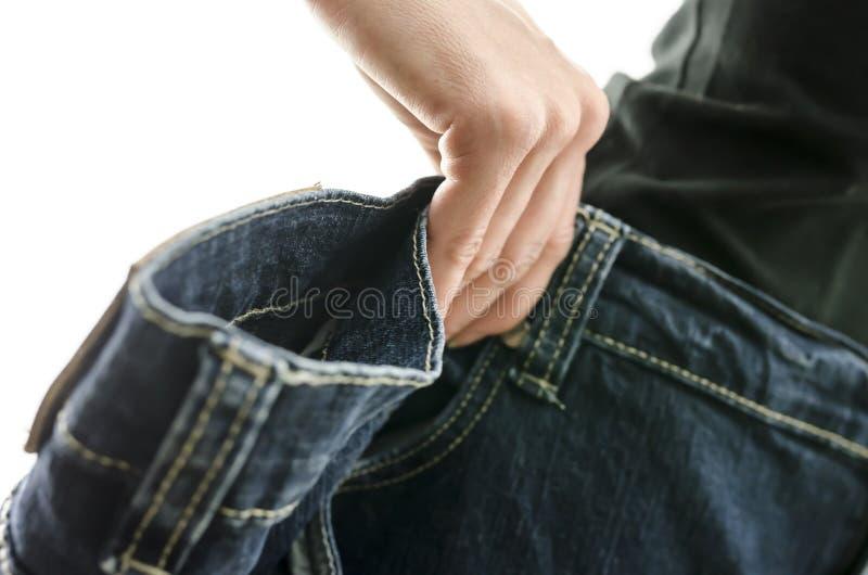 妇女皮包骨头的腰部细节在太大老牛仔裤的 免版税库存照片