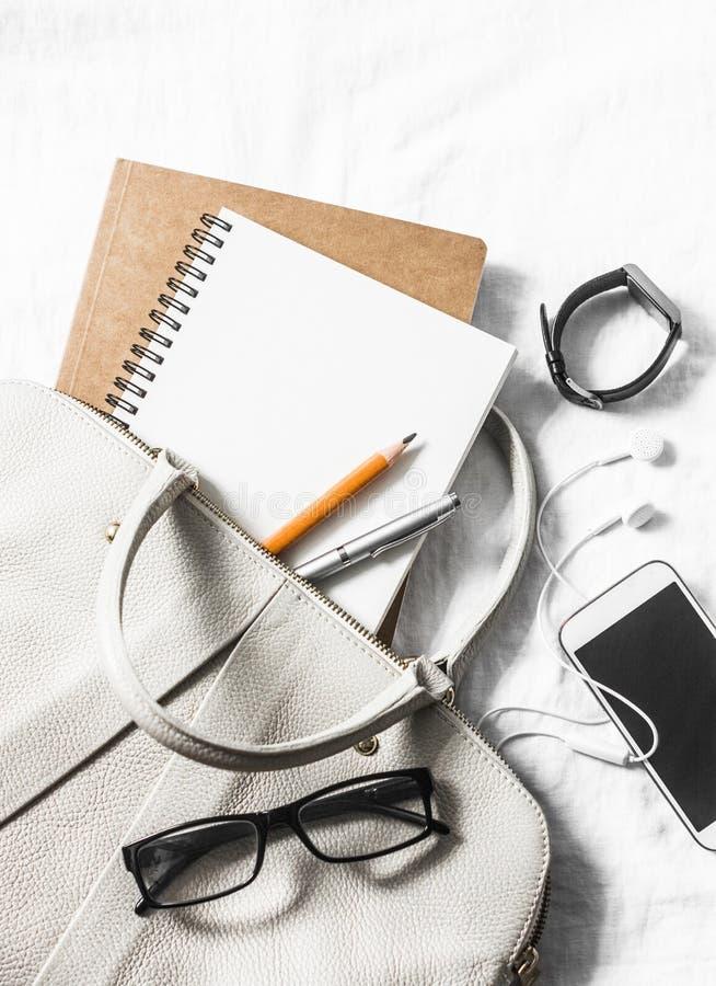 妇女皮革提包,干净的空白的笔记薄,笔,玻璃,智能手机,在轻的背景的手表,顶视图 文本的空位 库存图片