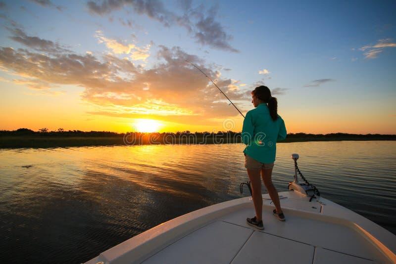 妇女盐水从小船的钓鱼铸件在日出期间 免版税库存图片