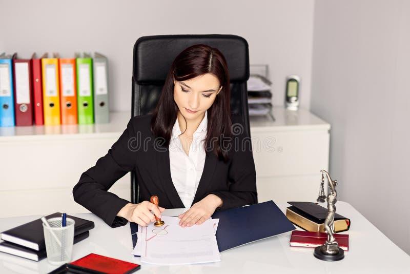 妇女盖印本文的公证人在她的办公室 免版税库存照片