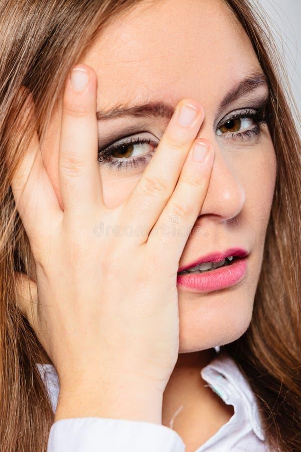 妇女盖子面孔神色通过手指 库存图片