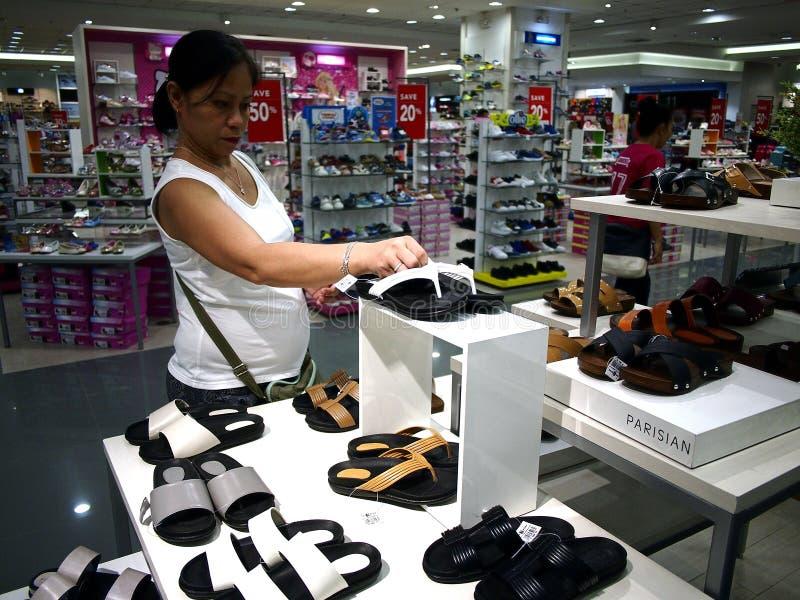 妇女看一双鞋在SM城市购物中心的鞋子部门的在Taytay市,菲律宾 免版税库存图片